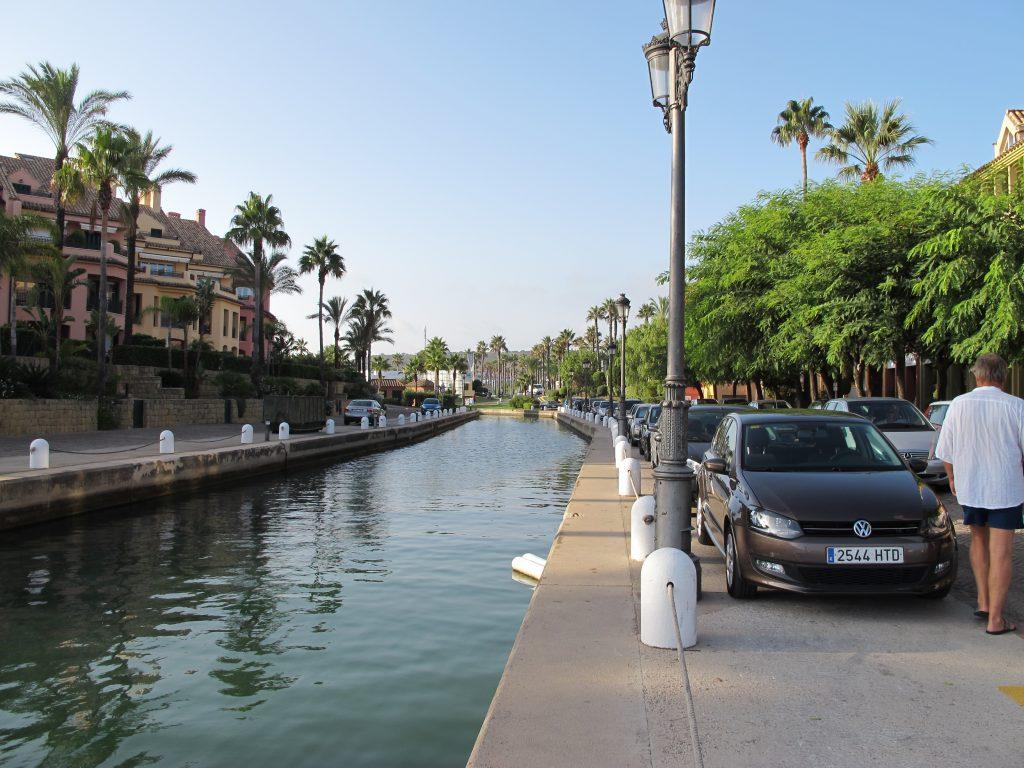 Stille kanaler omgitt av palmer og vakre bygninger