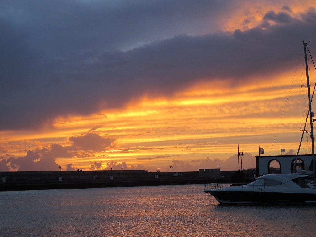 Mellom regnskyllene kommer solen frem, og solnedgangen viser seg frem.