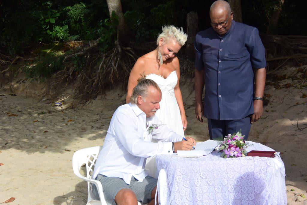 Brudgommen signerer vielsespapirene.